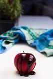 Gota de chocolate en la fruta roja de la manzana Fotografía de archivo