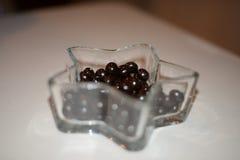 Gota de chocolate negro y dulce en el cuenco cristalino Foto de archivo