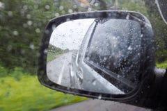 Gota de lluvia en el espejo de ala o el espejo del exterior del coche mientras que conduce en el camino en día lluvioso Conduzca  Imagenes de archivo