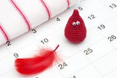 Gota de sangre divertida del ganchillo y un calendario Días críticos de la mujer, ciclo ginecológico de la menstruación Fotografía de archivo