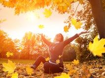 A gota feliz da mulher sae acima no parque do outono imagens de stock