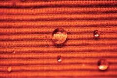 Gota macro da água em um pano colorido Fotos de Stock
