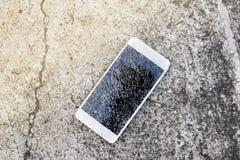 Gota quebrada do telefone celular no assoalho do cimento imagem de stock royalty free