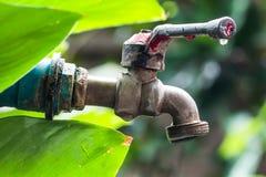 Gota velha e do grunge do torneira de bronze e da água no bokeh verde de t Foto de Stock Royalty Free