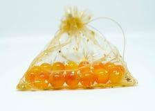 Gotas amarillo-naranja de la pulsera en un bolso del regalo Fotografía de archivo libre de regalías