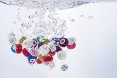 Gotas coloridas que caen en el agua Imágenes de archivo libres de regalías