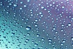 Gotas da água em um fundo azul-violeta Fotografia de Stock Royalty Free