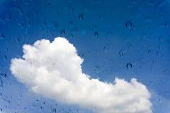 Gotas da água na janela de vidro sobre o céu azul Foto de Stock