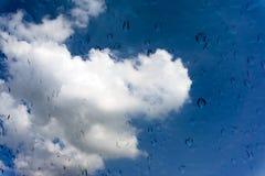 Gotas da água na janela de vidro sobre o céu azul Imagem de Stock Royalty Free