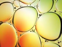 Gotas da água no óleo no fundo colorido Imagens de Stock