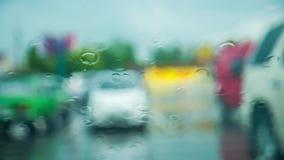 Gotas da água no vidro durante a chuva com carros sobre vídeos de arquivo
