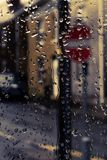 Gotas da chuva na janela com sinal de rua atrás imagem de stock