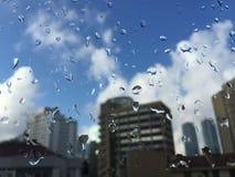 Gotas da chuva no windowpane contra construções Foto de Stock Royalty Free