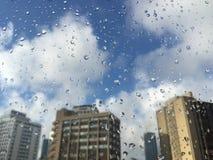 Gotas da chuva no windowpane contra construções Imagens de Stock