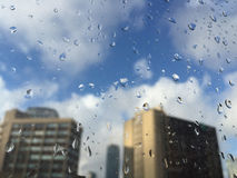 Gotas da chuva no windowpane contra construções Fotos de Stock Royalty Free
