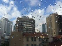 Gotas da chuva no windowpane contra construções Fotografia de Stock Royalty Free