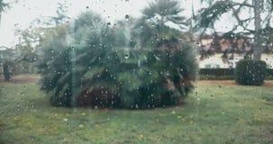 Gotas da chuva que caem para baixo no fundo azul de vidro, água filme