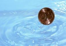 Gotas da moeda na água Fotografia de Stock Royalty Free