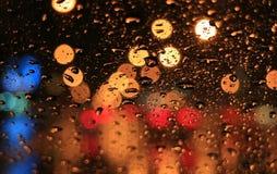 Gotas de agua en el parabrisas del coche con las luces borrosas del letrero a lo largo de la calle urbana en la noche fotografía de archivo libre de regalías