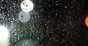 Gotas de agua sobre el vidrio contra la luz del bokeh de las luces de la noche metrajes