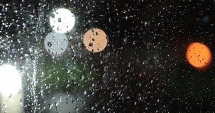 Gotas de agua sobre el vidrio contra la luz del bokeh de las luces de la noche almacen de metraje de vídeo