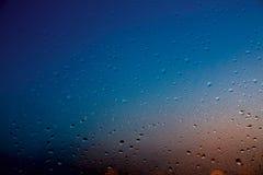Gotas de agua sobre el vidrio en azul y anaranjado Foto de archivo libre de regalías