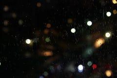 gotas de agua sobre el vidrio y las luces de la ciudad grande fotos de archivo