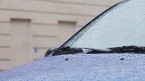 Gotas de agua y copos de nieve en el parabrisas y la carrocería del automóvil almacen de metraje de vídeo