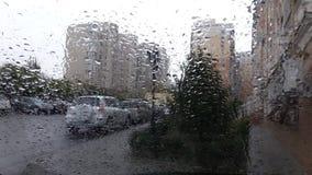 Gotas de la lluvia en el cristal de la ventanilla del coche metrajes