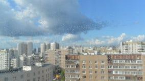 Gotas de la lluvia en un cristal de ventana, edificios adentro metrajes