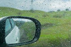 Gotas de la lluvia en la ventana y en el espejo de ala; prados verdes borrosos en el fondo Fotos de archivo libres de regalías