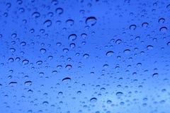 Gotas de lluvia azules en una ventana Imagenes de archivo