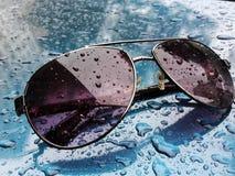 Gotas de lluvia en las gafas de sol imagenes de archivo