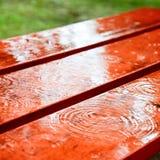Gotas de lluvia en un banco Fotos de archivo libres de regalías