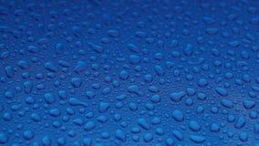 Gotas de lluvia en una superficie lisa azul