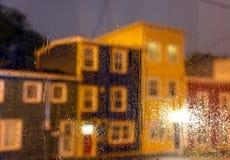 Gotas de lluvia en ventanas con las casas del jellybean en la noche en Terranova imagenes de archivo