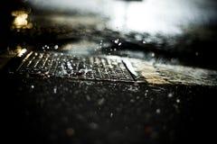 gotas de lluvia que bajan en el pavimento por noche Fotos de archivo