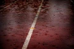 Gotas de lluvia que bajan en la pista corriente de la raza que retrasa competencias imagen de archivo