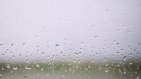 Gotas de lluvia que corren abajo en un vidrio de la ventana almacen de video