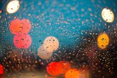 Gotas de lluvia sobre el vidrio del coche con el bokeh Foto de archivo