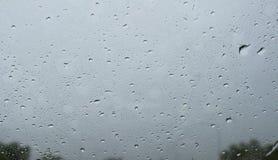Gotas de lluvia sobre el vidrio delantero del coche Fotos de archivo