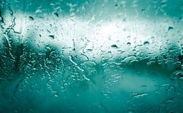 Gotas de lluvia sobre el vidrio verde del coche delantero fotos de archivo