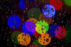 Gotas de lluvia y luces coloridas del color Imagenes de archivo