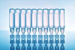 Gotas de olho dos rasgos no fundo azul das pipeta plásticas de cabeça para baixo imagem de stock royalty free