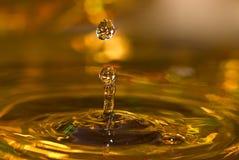 Gotas de oro del agua Foto de archivo libre de regalías