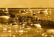 Gotas de oro del agua Imagen de archivo libre de regalías