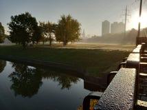 Gotas de orvalho na cerca perto do rio, cores do outono, névoa na água, opinião da cidade foto de stock royalty free