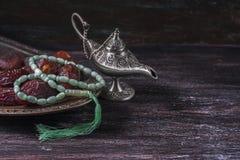 Gotas de rezo islámicas verdes, fechas y lámpara de plata del ` s del aladdin en un fondo de madera oscuro Concepto del Ramadán fotografía de archivo libre de regalías