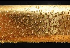 Gotas del agua en el metal de oro foto de archivo