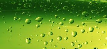 Gotas del agua en superficie verde Imagenes de archivo